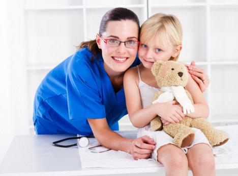 nurse hugging a young girl holding a teddy bear