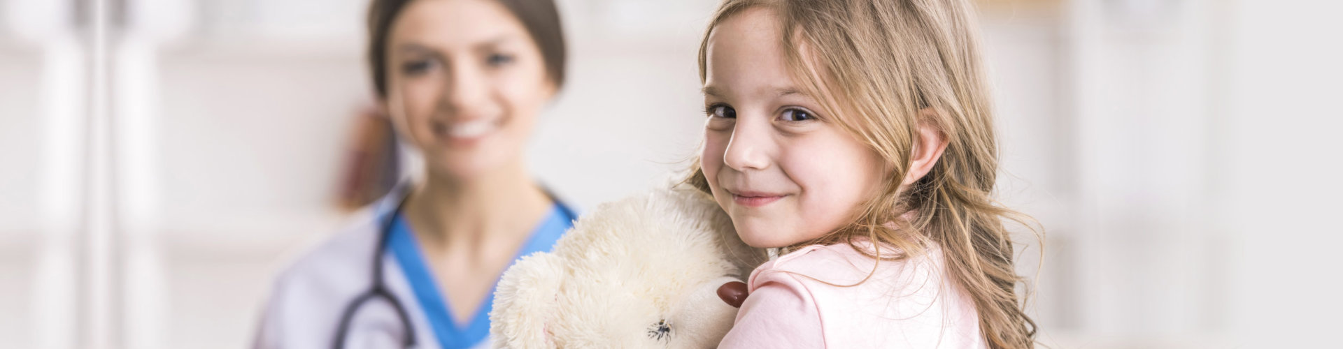 young girl holding her teddy bear with a therapist in the background